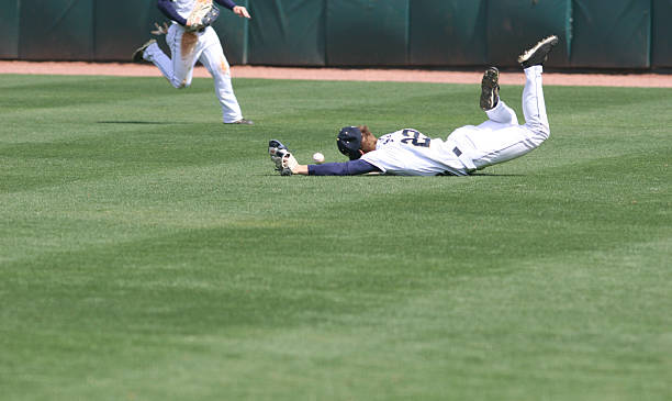 Man diving and missing the catch in baseball stock photo