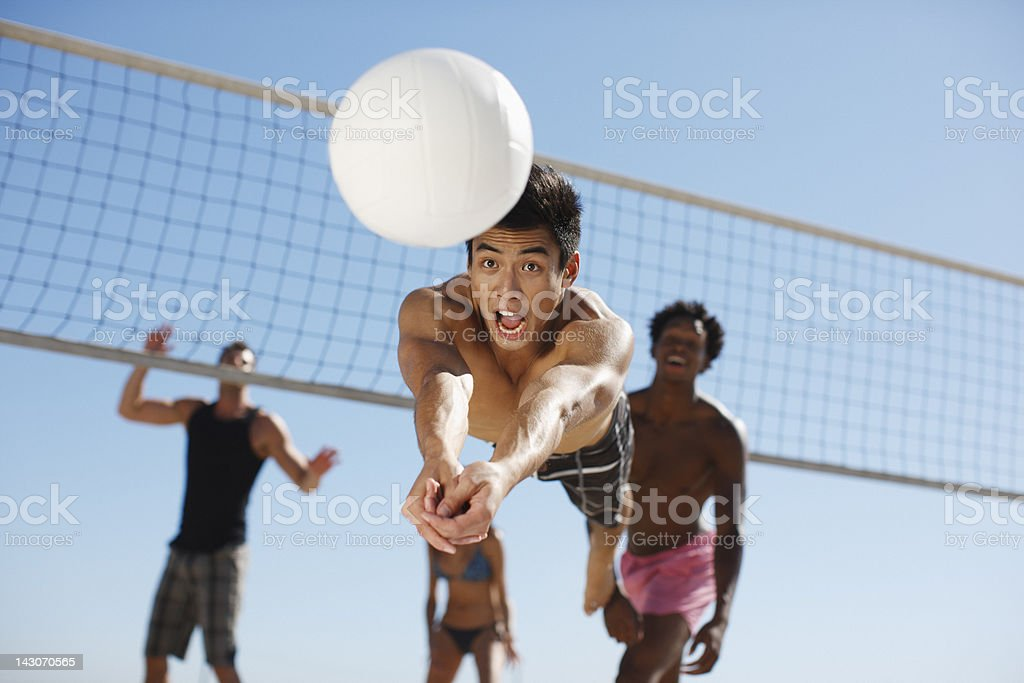 Man diving for volleyball on beach stock photo