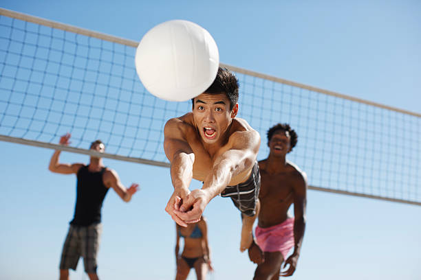 man diving for volleyball on beach - volleyball sport stock photos and pictures