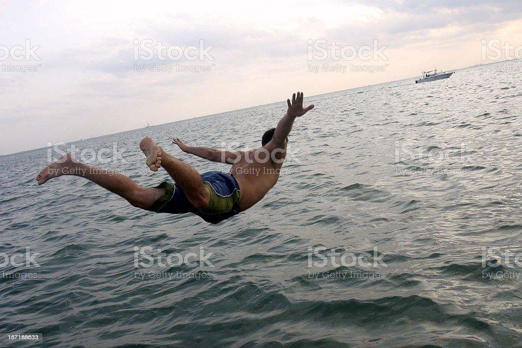 man diving in ocean stock photo