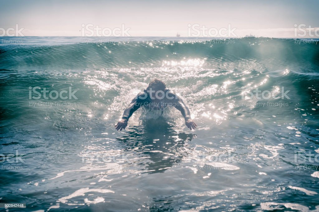 man diving into a wave in the ocean stock photo
