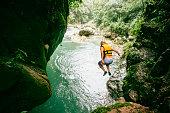 Man Jumps in the river at Puente de dios waterfall in San Luis Potosí. Mexico