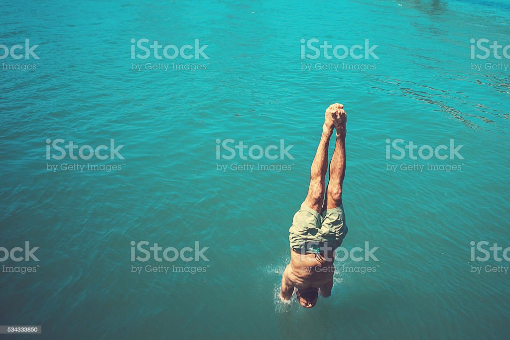 man diving into water stock photo