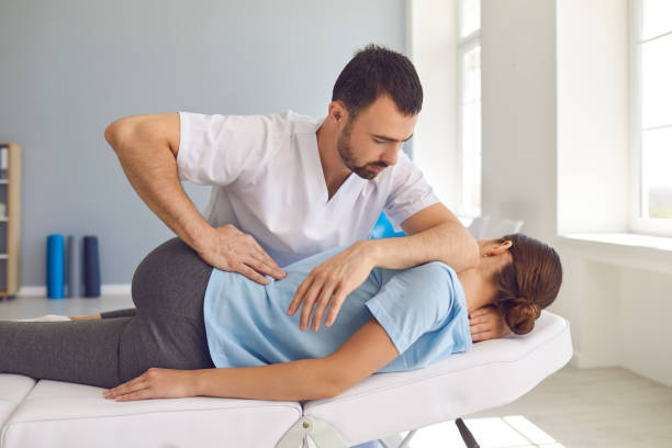 Man doctor chiropractor or osteopath fixing lying womans back in manual therapy clinic stock photo