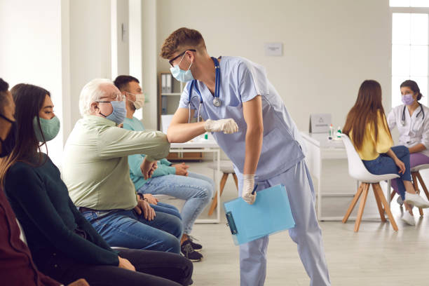 Man doctor in medical protective face mask bumping elbows with mature senior man patient before vaccination stock photo