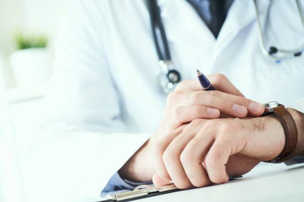 Mann Arzt mit Stethoskop mit Handgelenksuhr. Arzt in weißer Uniform am Bürohintergrund wartet auf Patienten. Zeit, Therapeuten zu besuchen. – Foto
