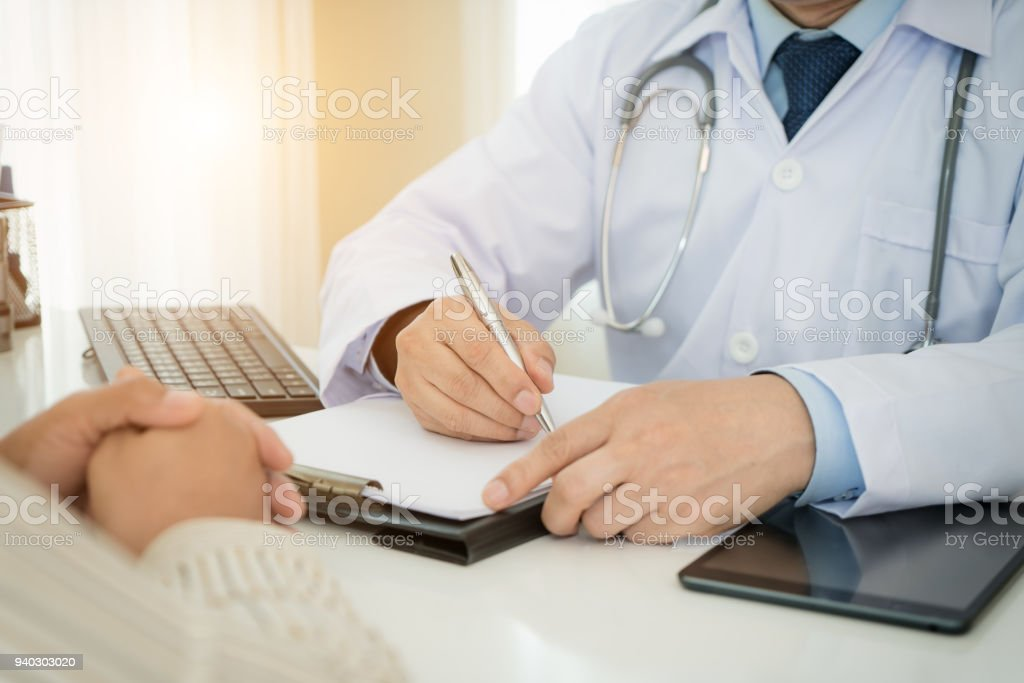 Man doctors and patient are discussing something for consultation. Medical Doctor working in hospital writing a prescription, Healthcare and medically concept stock photo