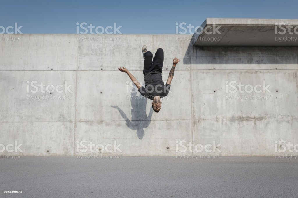 Man doing a back flip during parkour practice stock photo
