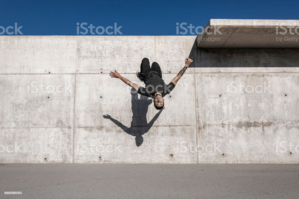 Man doing a back flip during parkour practice stock photo