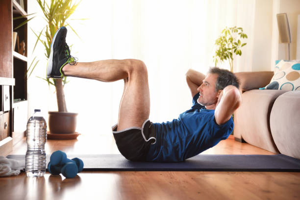 Man doing abdominal exercises lying down in living room stock photo