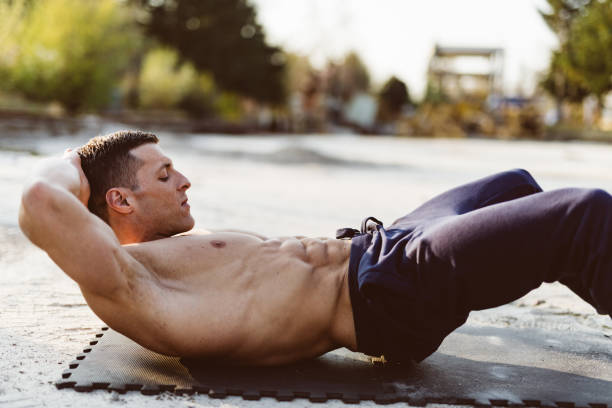 man doing abs exercise - milan2099 stock photos and pictures