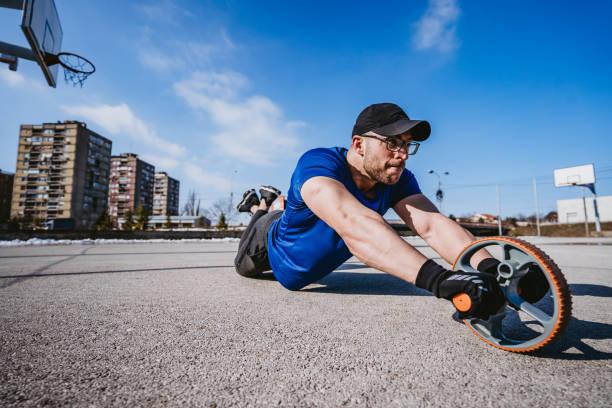 uomo che fa addominali con rullo ab all'aperto - man city exercise abs foto e immagini stock