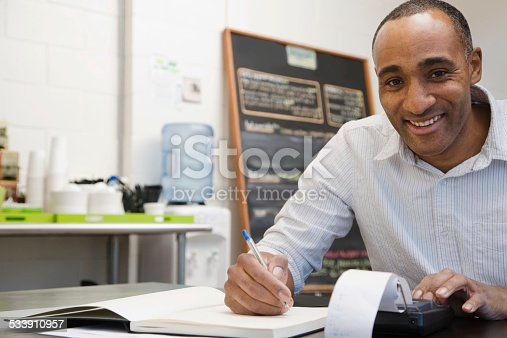 istock Man doing accounts in cafe 533910957