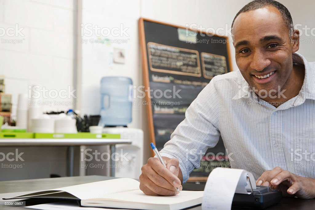Man doing accounts in cafe stock photo