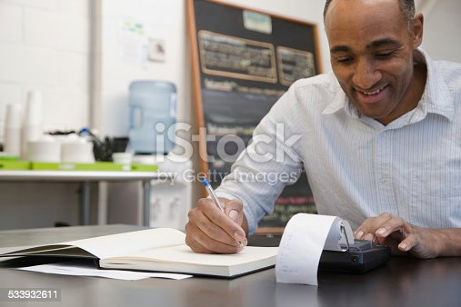 istock Man doing accounts in cafe 533932611