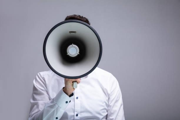 man doing announcement on megaphone - megafono foto e immagini stock