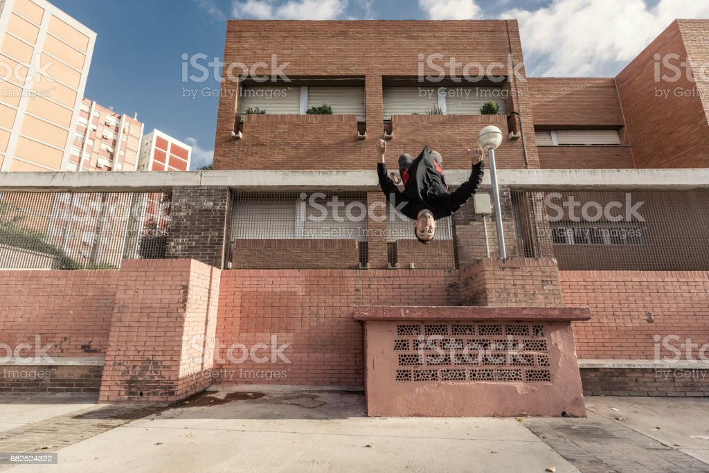 Young man practicing free running in the city