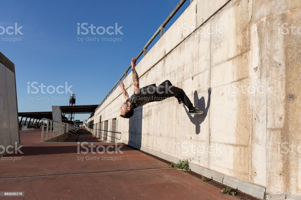 Man doing back flip while practicing parkour in the city stock photo