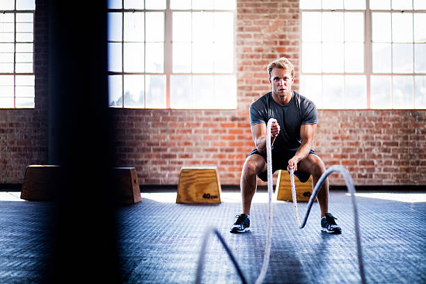 Man doing battle ropes exercise during gym training at gym stock photo