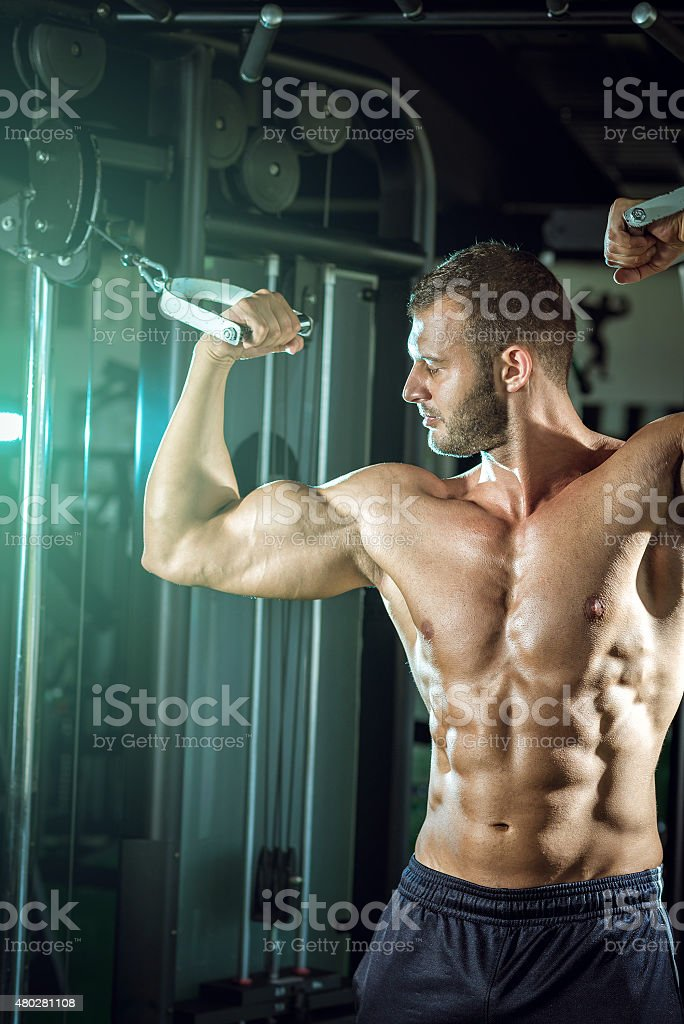 Man doing cable fly in gym stock photo
