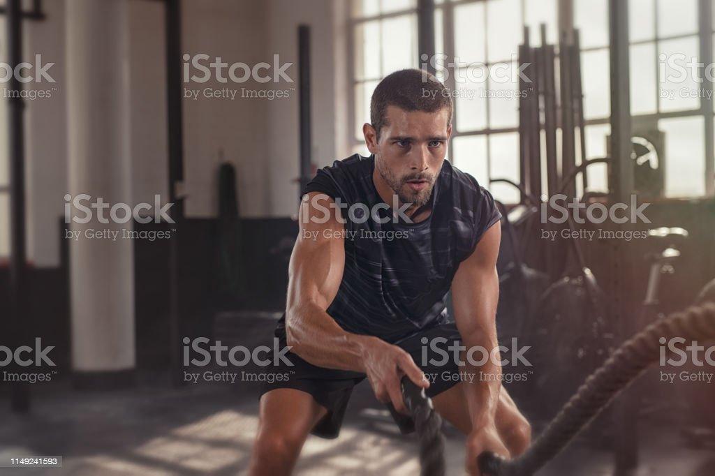 Man doing cross training exercise with rope - Zbiór zdjęć royalty-free (20-29 lat)