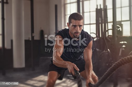 Athletic young man doing some cross training exercises with a rope. Determined fit guy doing battle ropes exercise at the cross training gym. Handsome man training with effort.