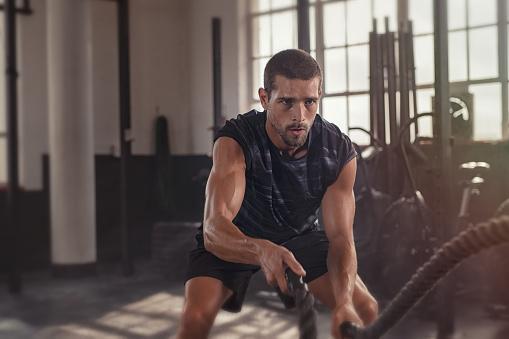 Man Doing Cross Training Exercise With Rope - zdjęcia stockowe i więcej obrazów 20-29 lat