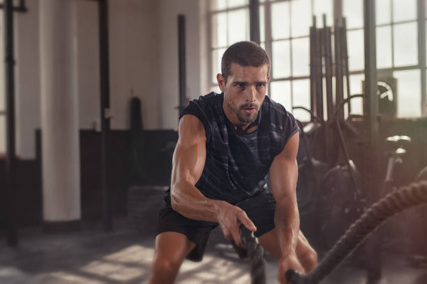 Man doing cross training exercise with rope Athletic young man doing some cross training exercises with a rope. Determined fit guy doing battle ropes exercise at the cross training gym. Handsome man training with effort. exercising stock pictures, royalty-free photos & images