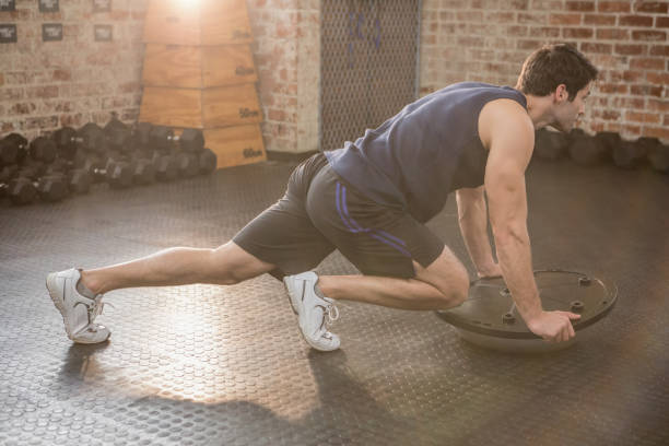 Man doing exercise with bosu ball stock photo