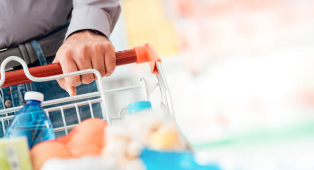 Man doing grocery shopping Man doing grocery shopping at the supermarket, he is pushing a full trolley, hand detail close up discount store stock pictures, royalty-free photos & images