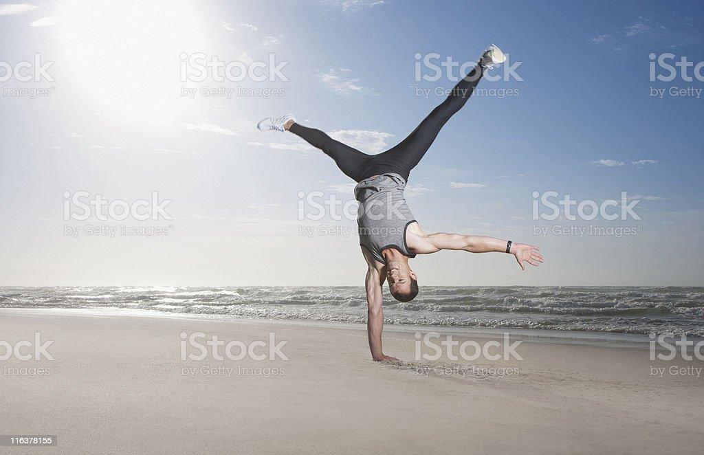 Man doing handstand on beach stock photo