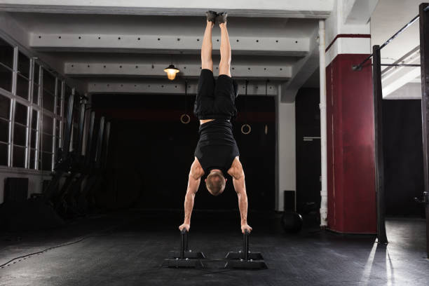 man doing handstand on parallel bar - peso mosca foto e immagini stock