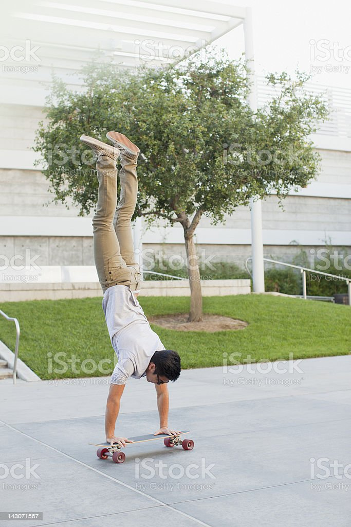 Man doing handstand on skateboard royalty-free stock photo