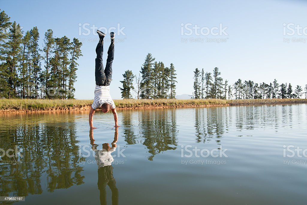 Man doing handstand on water stock photo
