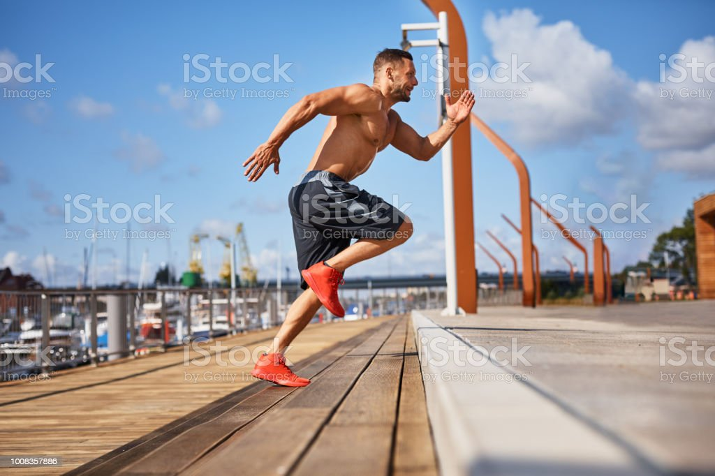 man doing hit exercises on stairs outdoors stock photo