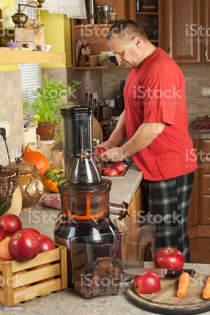 Man doing in the kitchen apple juice with carrot. photo libre de droits
