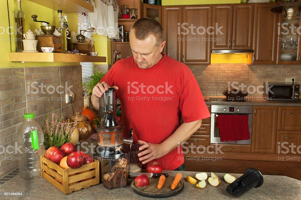 Man doing in the kitchen apple juice with carrot. Lizenzfreies stock-foto