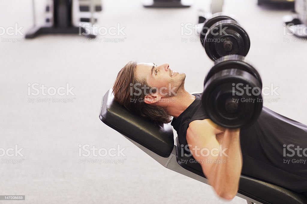 Man doing incline chest presses with dumbbells in gymnasium royalty-free stock photo