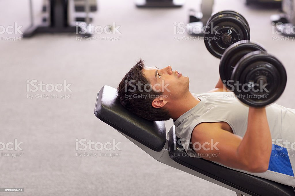 Man doing incline chest presses with dumbbells in gymnasium stock photo