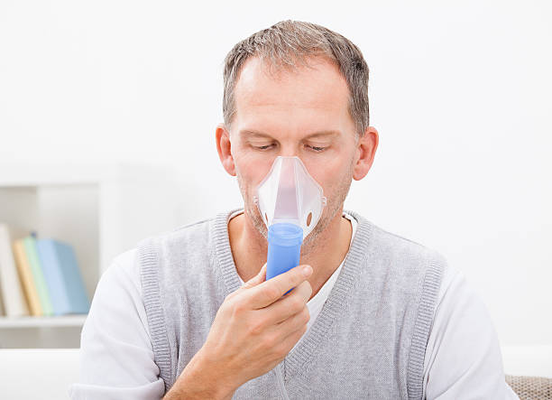 Man Doing Inhalation Man Doing Inhalation Through Oxygen Mask At Home oxygen mask stock pictures, royalty-free photos & images