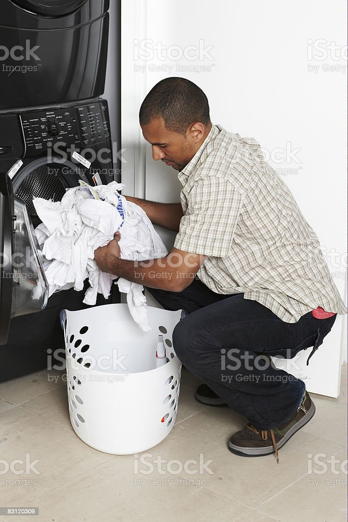 Man doing laundry in utility room royalty free stockfoto