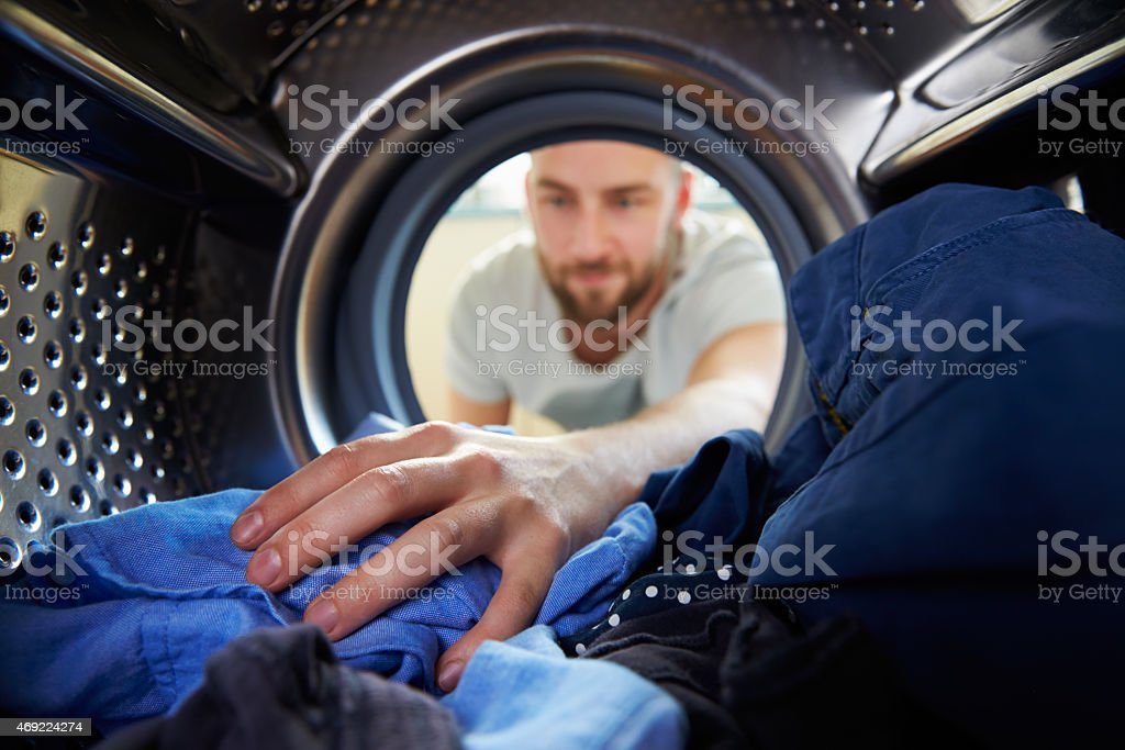 Man Doing Laundry Reaching Inside Washing Machine stock photo