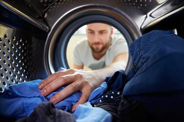 man ている室内の洗濯機のランドリー - 衣類乾燥機 ストックフォトと画像