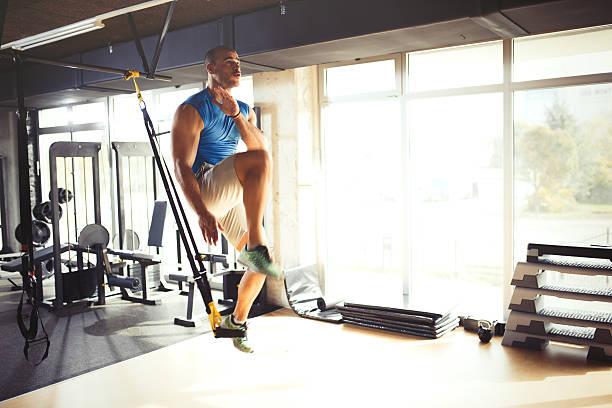 Man doing leg exercises with suspension straps at gym. stock photo