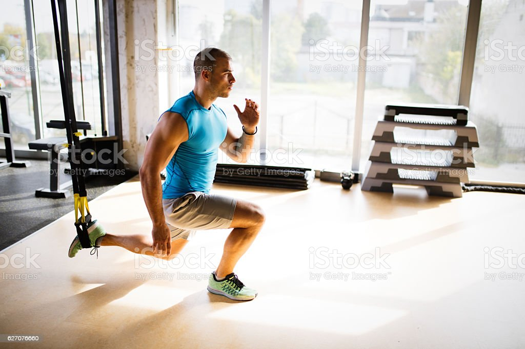 Man doing leg exercises with suspension straps at gym. stock photo