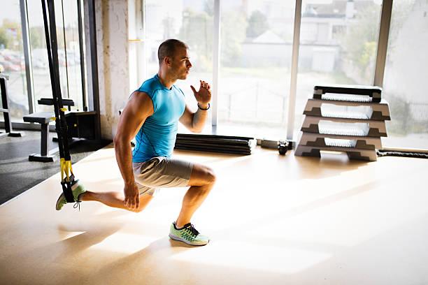 Man doing leg exercises with suspension straps at gym. - foto de stock