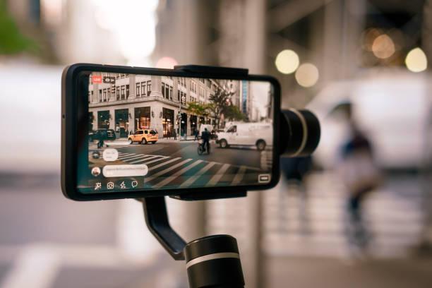mann macht live-video mit telefon mit stabilisator in ny - fotohandy stock-fotos und bilder
