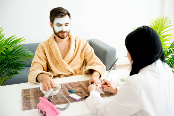 Man doing manicure A spa worker does a manicure for a handsome man pedicure manicure men beauty spa stock pictures, royalty-free photos & images