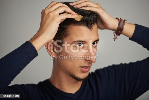 istock Man doing modern hairstyle 854349238