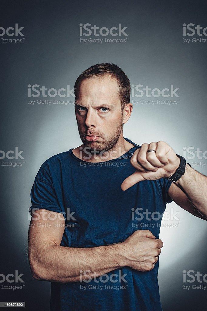 Man doing negative thumbs down in studio stock photo